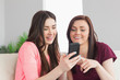 Two smiling girls sitting on a sofa and typing on a mobile phone