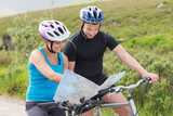Couple on mountain bikes reading map