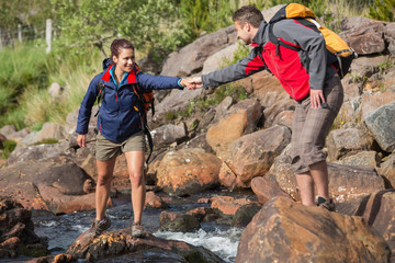 Man helping his smiling girlfriend to cross a river