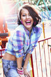 Enjoyment. Gladness. Woman in Checkered Shirt with Toothy Smile