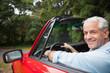 Smiling handsome man driving red cabriolet