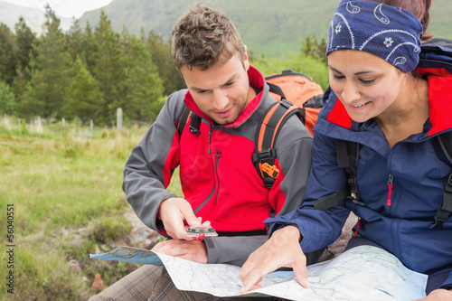 Couple using map and compass to find the way