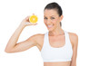 Happy woman in sportswear holding slice of orange
