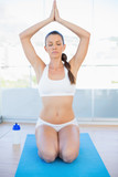 Peaceful sporty woman sitting in yoga position on exercise mat