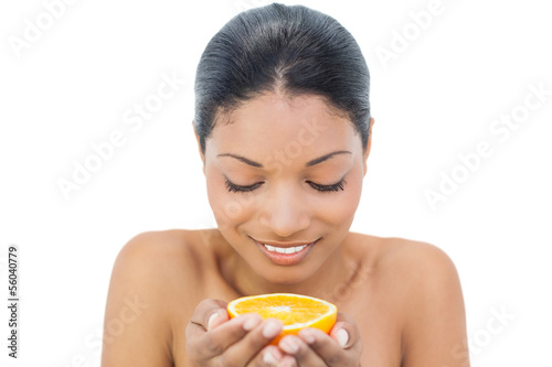 Cheerful black haired model holding orange slice
