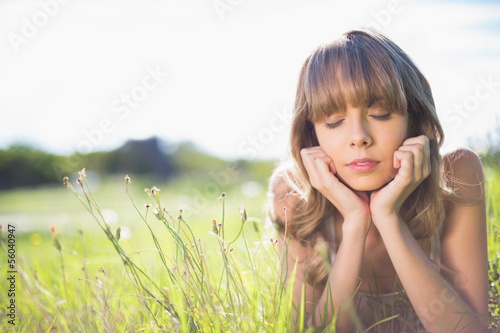 Pensive young woman lying on the grass