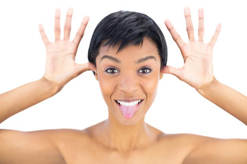 Joyful black haired woman posing with tongue out and hands aroun
