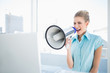 Furious elegant woman shouting in megaphone