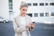 Serious stylish businesswoman sending a text