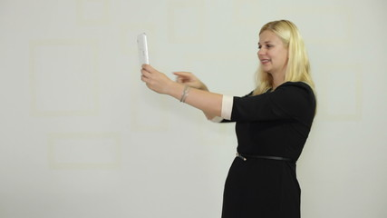 Happy woman enjoying taking photos with digital tablet