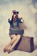 Redhead girl with binocular sitting on the big suitcase