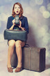 Redhead girl with camera sitting on the big suitcase