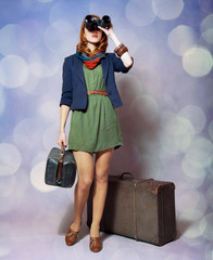 Redhead girl with binocular standing near the big suitcase