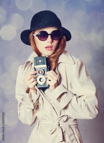 Redhead girl in cloak with camera as a spy