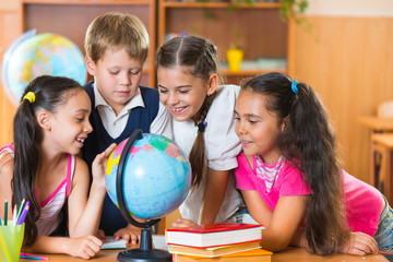 Portrait of cute schoolchildren looking at globe