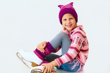 cheerful girl sitting on ice skates