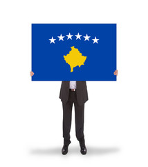 Businessman holding a big card, flag of Kosovo