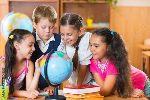 Plagát Portrait of cute schoolchildren looking at globe