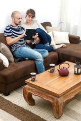 Jeune couple dans un sofa regardant une tablette