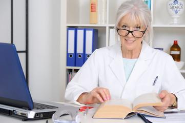 Senior Ärztin schlägt im Fachbuch nach.