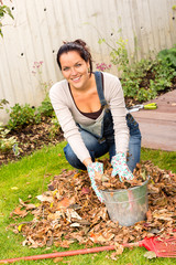 Happy woman filling bucket leaves fall gardening