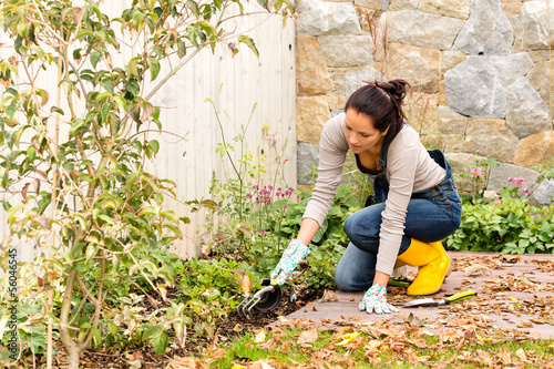 Young woman planting backyard flowerbed autumn