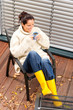 Cheerful woman drinking tea autumn rubber boots
