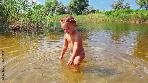 little girl playing in the river