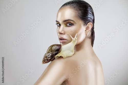 Beauty portrait of a young woman holding snail