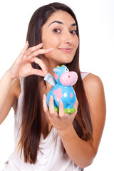 beautiful young woman with a cow piggy bank