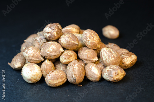 Handful of whole hazel nuts isolated on black