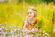 Beautiful european blond girl with bouquet of wild flowers