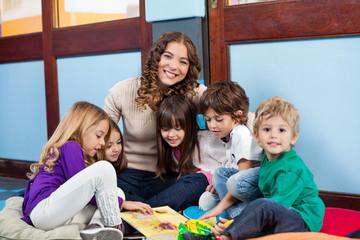 Teacher Sitting With Children On Floor