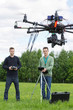 Technicians Flying UAV Helicopter in Park