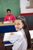 Schoolgirl Sitting At Desk With Teacher Smiling In Background