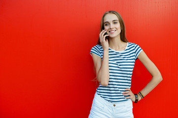 Young happy woman talking on mobile phone near red wall