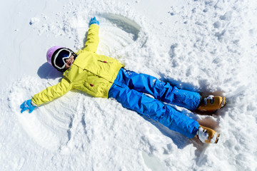 Winter fun - Snow Angel - young girl playing in snow