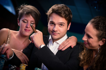 Man with glamorous women in casino at poker table