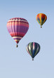 Three Hot-Air Balloons Floating against a Blue Sky