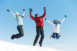 Three jumping young people in winter