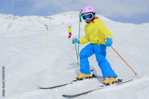 Skiing, skiers on ski run - child skiing downhill