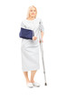 Blond female patient in gown with broken arm and crutch