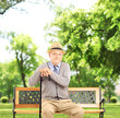 Senior man sitting on a bench and looking at camera, in a park