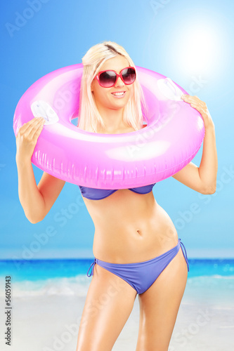 Blond female in bikini holding a swimming ring on a beach