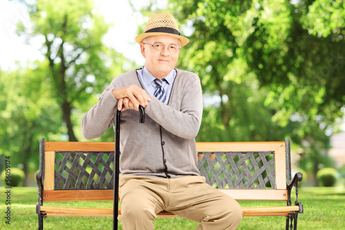 Senior man sitting on a wooden bench, in a park