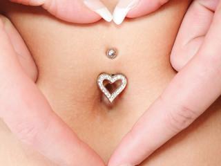 hands heart symbol around navel piercing