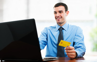 Man using a credit card in front of his laptop
