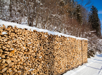 Firewood stacked in winter.  Wood pile with snow stacked for fir