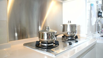 Metal pots on a stove in a white kitchen