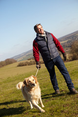 Man Taking Dog On Walk In Autumn Countryside